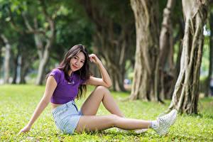Fotos Asiatische Gras Sitzen Bein Shorts T-Shirt Lächeln Blick junge Frauen