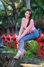 Fotos Asiaten Posiert High Heels Jeans Lächeln Starren Unscharfer Hintergrund Bein junge frau
