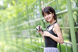 Hintergrundbilder Asiatische Lächeln Fotoapparat Starren Mädchens