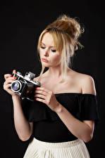 Bilder Carla Monaco Blond Mädchen Bluse Hand Fotoapparat Schwarzer Hintergrund Mädchens