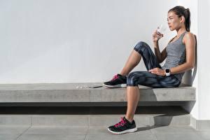 Fotos Fitness Sitzt Unterhemd Trinkglas Trinkt Wasser Erholung Mädchens