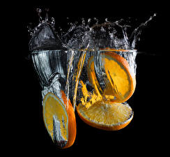 Pictures Orange fruit Water Black background Water splash Piece Three 3 Food