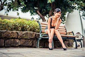 Fotos Asiatische Sitzend Bank (Möbel) Bein Kleid Dekolleté Starren junge Frauen