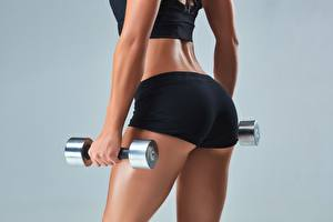 Desktop hintergrundbilder Fitness Großansicht Hantel Hand Gesäß Grauer Hintergrund Shorts hips sportliches Mädchens
