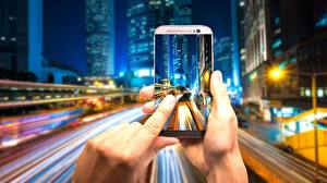 Pictures Skyscrapers Blurred background Hands Smartphones Photographer Night time Cities