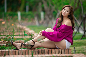 Image Asiatic Brown haired Sit Legs Shorts Glance Blurred background young woman