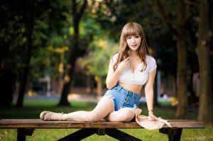 Fotos Asiatische Braune Haare Sitzen Bein Shorts Unterhemd Hand Blick Tisch Mädchens