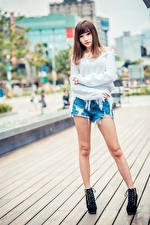 Pictures Asiatic Posing Legs Shorts Sweater Staring Blurred background young woman