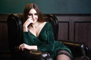 Pictures Brown haired Armchair Sitting Gown Décolletage Smile Staring Denis Kornilov female