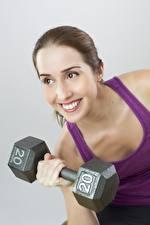 Fotos Fitness Grauer Hintergrund Braune Haare Starren Lächeln Hanteln 20 junge frau
