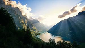 Фотографии Горы Озеро Швейцария Альпы Лучи света Klontalersee