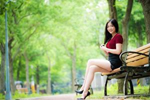 Bilder Asiaten Bank (Möbel) Bokeh Brünette Lächeln Hand Sitzen Bein Stöckelschuh junge Frauen