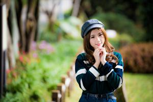 Pictures Asiatic Bokeh Brown haired Baseball cap Hands Smile Glance Lovely young woman