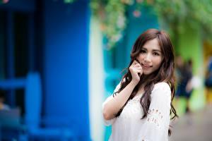 Tapety na pulpit Azjatycka Rozmazane tło Brązowowłosa dziewczyna Wzrok Uśmiech Ręce dziewczyna