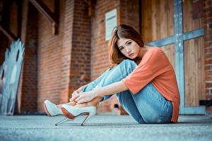 Picture Asiatic Blurred background Brown haired Hands Sit Legs Jeans High heels Beautiful young woman