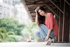 Tapety na pulpit Azjaci Bokeh Brązowowłosa dziewczyna Siedzi Ręce Nogi Buty na obcasie Dżinsy młoda kobieta