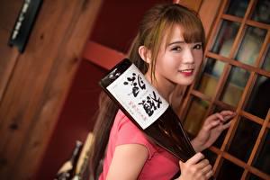 Bilder Asiaten Braune Haare Starren Lächeln Flasche Mädchens
