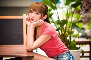 Bilder Asiatisches Braunhaarige Sitzt Starren Hand Unscharfer Hintergrund