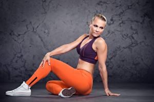 Fotos Fitness Pose Blond Mädchen Sitzt Hand Bein Plimsoll Schuh junge Frauen