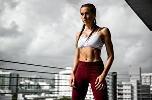 Bureaubladachtergronden Fitness Pose Vlecht Hand Buik Kijkt jonge vrouw