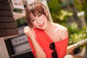 Tapety na pulpit Azjatycka Rozmazane tło Dziewczyna z brązowymi włosami Wzrok Uśmiech Okulary Ręce młode kobiety