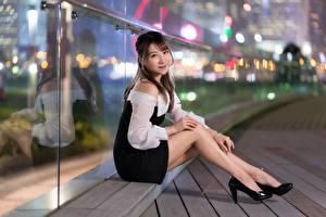 Fotos Asiatische Braunhaarige Bokeh Lächeln Sitzen Hand Bein Stöckelschuh junge Frauen