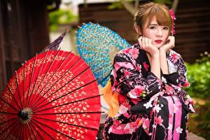 Tapety na pulpit Azjaci Brązowowłosa dziewczyna Parasol Kimono Ręce Siedzą Spojrzenie dziewczyna