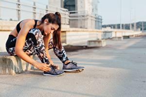 Bilder Fitness Braunhaarige Sitzt Hand Bein Turnschuh Mädchens