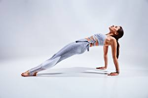 Pictures Fitness Gray background Pose Hands Legs Plank (exercise) young woman