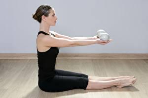 Bilder Fitness Seitlich Trainieren Sitzend Hand Bein junge Frauen