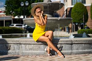 Desktop wallpapers Fountains Frock Yellow Hat Hands Smile Beautiful Legs Sit Posing Olga young woman