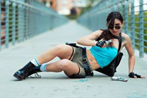 Pictures Pistol Brunette girl Lying down Hands Eyeglasses Glove Shorts Legs Boots Cosplay Lara Croft young woman