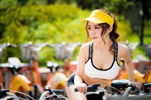 Bilder Asiaten Baseballkappe Unscharfer Hintergrund Braune Haare Starren Hand Fahrrad Mädchens