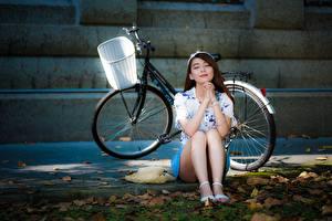 Fotos Asiaten Fahrrad Der Hut Braune Haare Sitzt Hand Bein junge frau