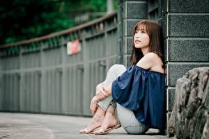 Fotos Asiaten Unscharfer Hintergrund Braunhaarige Sitzt Hand Bein junge Frauen