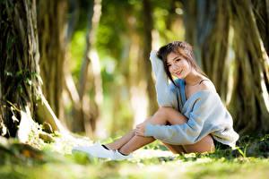 Bilder Asiaten Bokeh Braune Haare Lächeln Sitzt Sweatshirt Hand junge Frauen