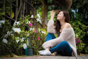 Fotos Asiatische Unscharfer Hintergrund Sitzen Hand Bein Lächeln Sweatshirt junge Frauen