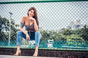 Pictures Asian Fence Sitting Jeans Smile Glance Legs Girls