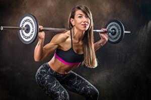 Fotos Fitness Körperliche Aktivität Pose Hand Hantelstange Starren Braune Haare Kauert sportliches Mädchens