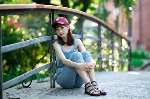 Bureaubladachtergronden Aziaten Een hek Bruin haar vrouw Baseballpet Zittend Hand Benen Onscherpe achtergrond jonge vrouw
