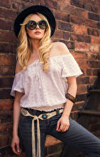Images Carla Monaco Blonde girl Posing Wall Made of bricks Hat Blouse Eyeglasses Jeans Glance young woman
