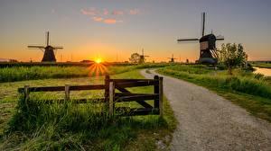 Bakgrundsbilder på skrivbordet Nederländerna Gryning och solnedgång Väg Väderkvarn Gräset Staket Kinderdijk Natur