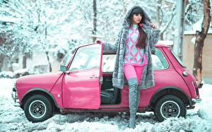 Pictures Winter Snow Pink color Pose Brunette girl Fur coat Sweater Hands Legs Wearing boots young woman Cars