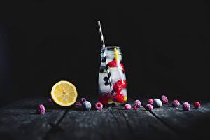 Pictures Drinks Lemons Raspberry Black background Wood planks Jar Ice Food