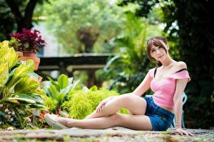 Hintergrundbilder Asiatisches Braune Haare Sitzend Shorts Bein Unscharfer Hintergrund Mädchens