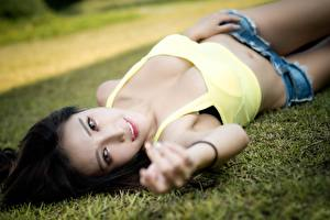 Fotos Asiaten Brünette Gras Unscharfer Hintergrund Liegen Shorts Hand Starren junge frau