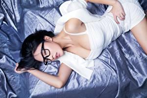 Bilder Asiatische Brünette Liegt Brille Blick Hand junge Frauen