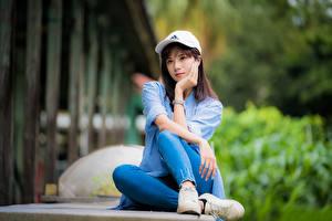 Fotos Asiaten Sitzt Jeans Hemd Baseballmütze Starren Unscharfer Hintergrund junge frau