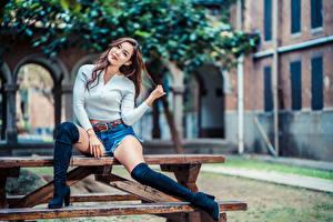 Fotos Asiaten Sitzt Bein Shorts Starren Unscharfer Hintergrund junge frau