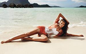 Bilder Meer Strand Hinlegen Posiert Shorts Braune Haare Nass Bein Mädchens